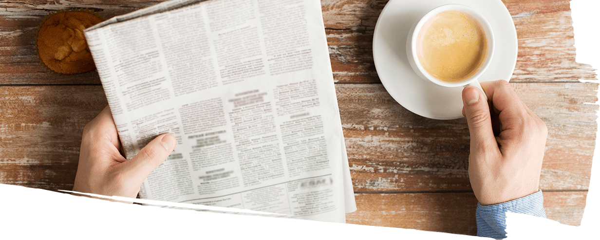 Man enjoying espresso while reading the newspaper