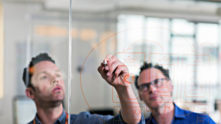 Businessman drawing diagram on glass wall in tech start-up office